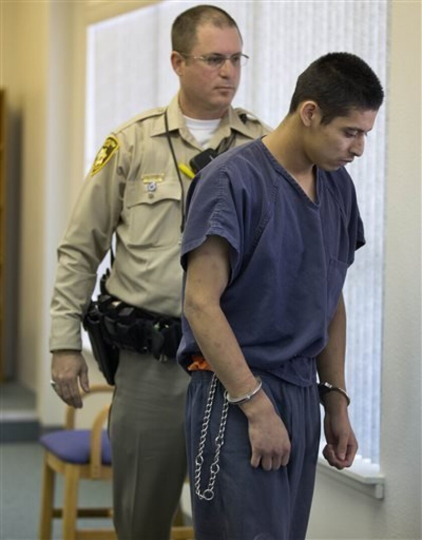 FILE - This April 10, 2013 file photo shows Jean Ervin Soriano, right, leaving Moapa District Court, in Moapa, Nev. Soriano, an 18-year-old accused of driving drunk in a Nevada crash that killed five California family members was cleared of charges Wednesday July 10, 2013, after DNA evidence showed his friend was the one driving the SUV. (AP Photo/Julie Jacobson, file )