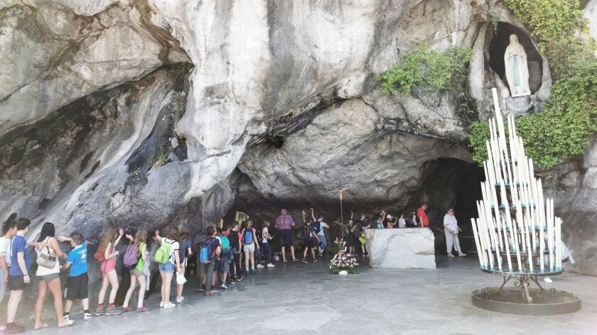 LOURDES, France Ð JUNE 18, 2019: Tourists walk through the grotto where Bernadette claimed the mothe