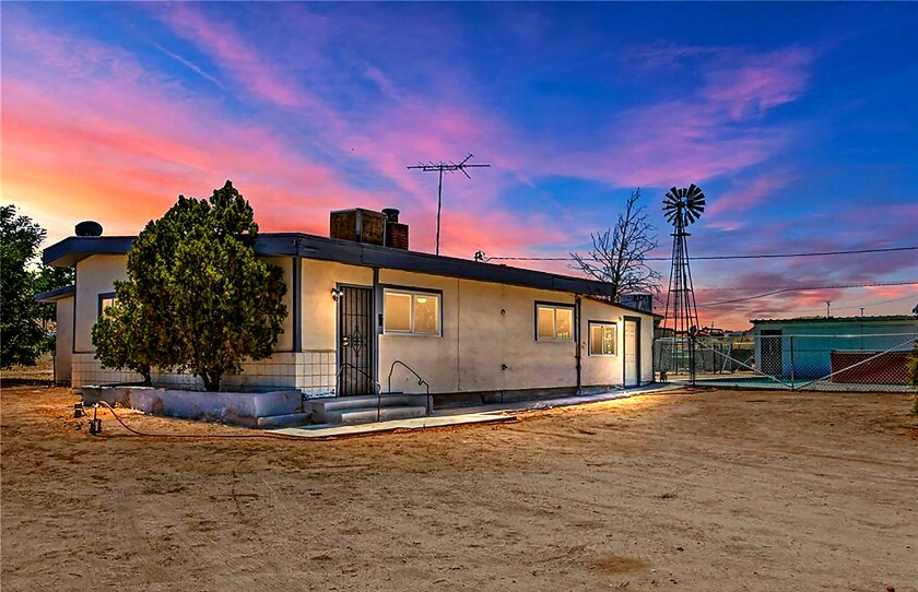The exterior of a small, single-story home on a dirt lot at 17481 Coad Road, Victorville