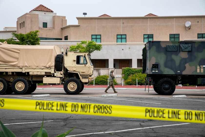 National Guard troops gather equipment from vehicles parked outside the La Mesa Civic Center.