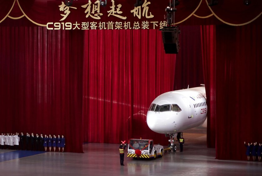 Chinese workers wave as a truck pulls out the first twin-engine 158-seater C919 passenger plane made by The Commercial Aircraft Corp. of China (COMAC) during a ceremony at the company's hangar near the Pudong International Airport in Shanghai, China, Monday, Nov. 2, 2015. The first plane produced b