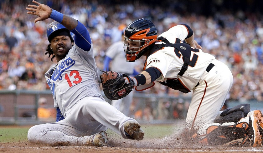 Dodgers shortstop Hanley Ramirez (13) beats the tag of Giants catcher Buster Posey to score in a game earlier this season. The two middle-of-the-order hitters could plays vital roles in a division race that heats up this weekend.