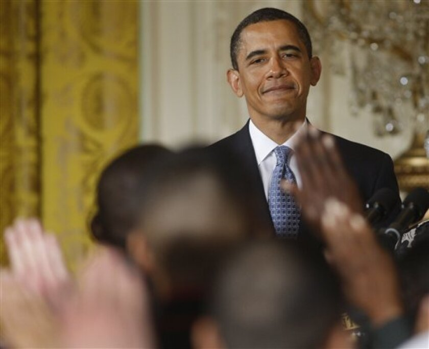 President Barack Obama smiles as he looks out at the raise hands as members of the military being sworn-in as U. S. citizens during a naturalization ceremony, Friday, May 1, 2009, for active duty service members in the East Room of the White House in Washington. (AP Photo/Ron Edmonds)