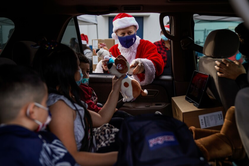 A man dressed as Santa hands gifts to students through a car window