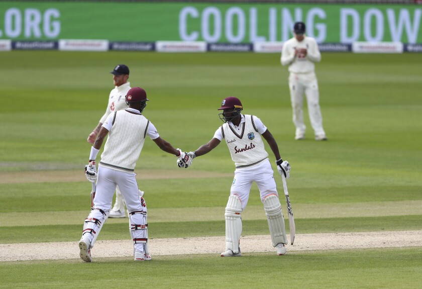 West Indies' Shamarh Brooks, right, shakes hands with Roston Chase after scoring fifty runs during the fourth day of the second cricket Test match between England and West Indies at Old Trafford in Manchester, England, Sunday, July 19, 2020. (Michael Steele/Pool via AP)