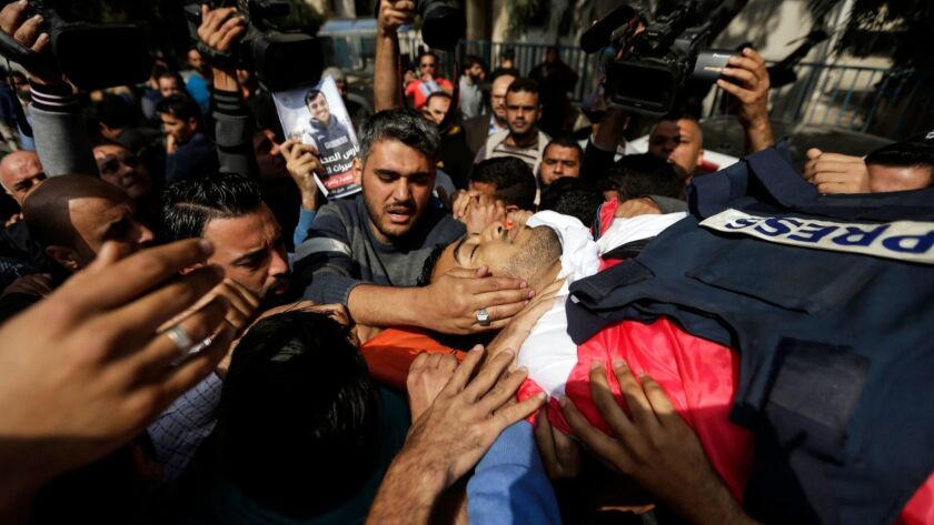 Journalists and other mourners carry the body of Palestinian journalist Yasser Murtaja during his funeral in Gaza City on April 7, 2018. Murtaja, a photographer with Gaza's Ain Media agency, was among those shot dead during Friday's clash between Israeli forces and Palestinians.