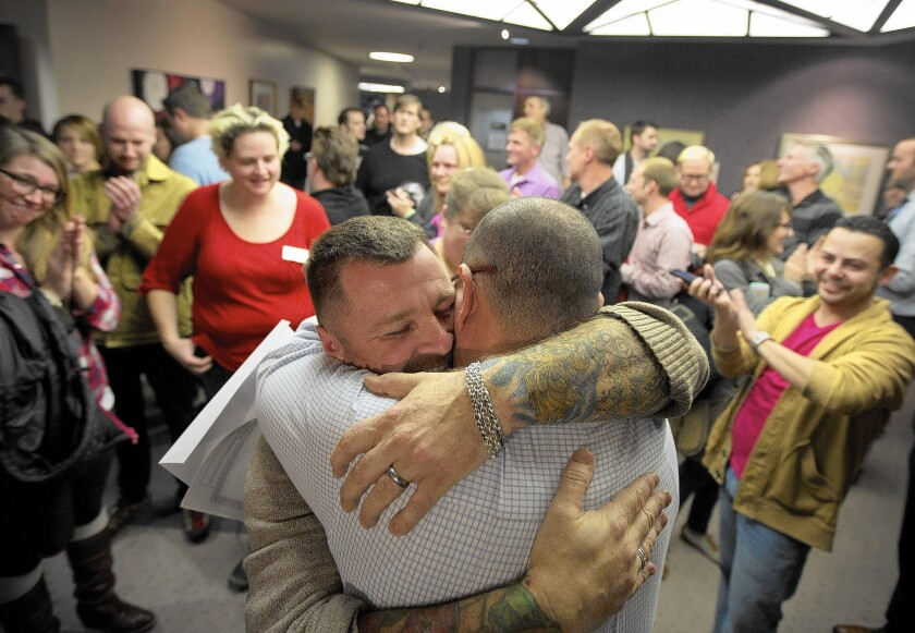 Chris Serrano, left, and Clifton Webb embrace after being married in Salt Lake City in December.