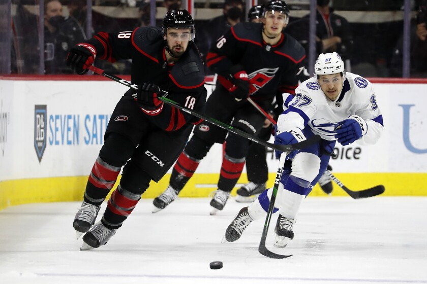 Carolina Hurricanes' Cedric Paquette (18) and Tampa Bay Lightning's Yanni Gourde (37) chase the puck during the second period of Game 2 of an NHL hockey Stanley Cup second-round playoff series in Raleigh, N.C., Tuesday, June 1, 2021. (AP Photo/Karl B DeBlaker)