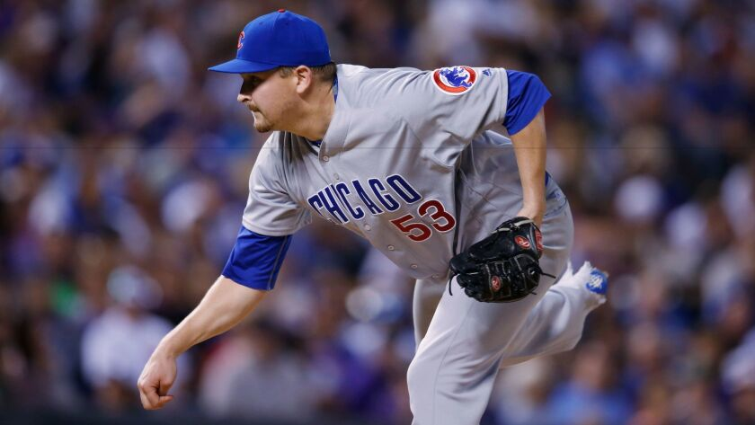 Cubs relief pitcher Trevor Cahill watches a delivery to the Rockies' Chris Rusin during the sixth inning of a baseball game Saturday, Aug. 20, 2016 in Denver. The Cubs won 9-2.
