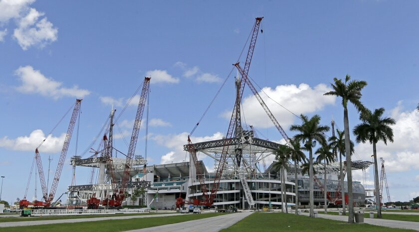 Construction cranes rise above the Miami Dolphins' NFL football stadium, where crews are working around the clock to complete the latest phase in a $500 million renovation before the season starts, Thursday, June 2, 2016, in Miami Gardens, Fla. (AP Photo/Alan Diaz)