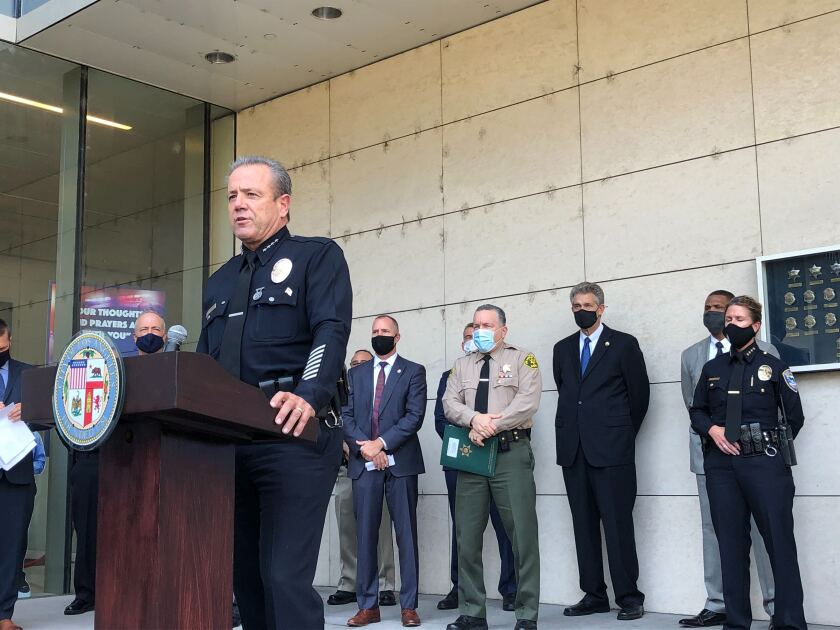 LAPD Chief Michel Moore speaks at a lectern with other masked law enforcement leaders standing behind him outside LAPD HQ