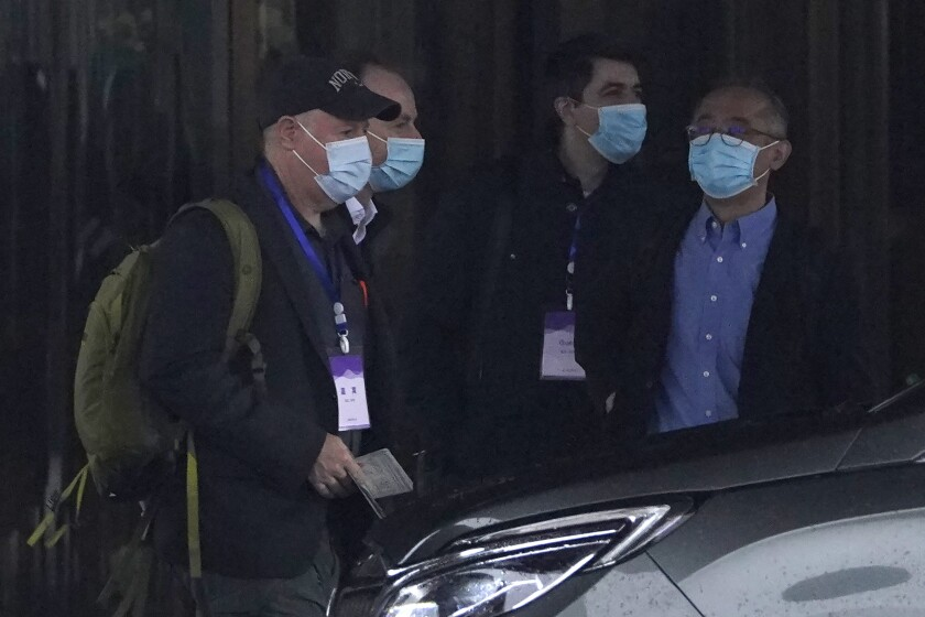 Members of the World Health Organization team including Peter Daszak, left, Ken Maeda, right, and Vladimir Dedkov, second right, prepare to leave for a fourth day of field visits from their hotel in Wuhan in central China's Hubei province on Monday, Feb. 1, 2021. (AP Photo/Ng Han Guan)