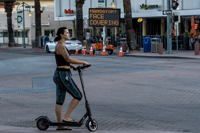 A woman travels on a scooter in downtown Palm Springs