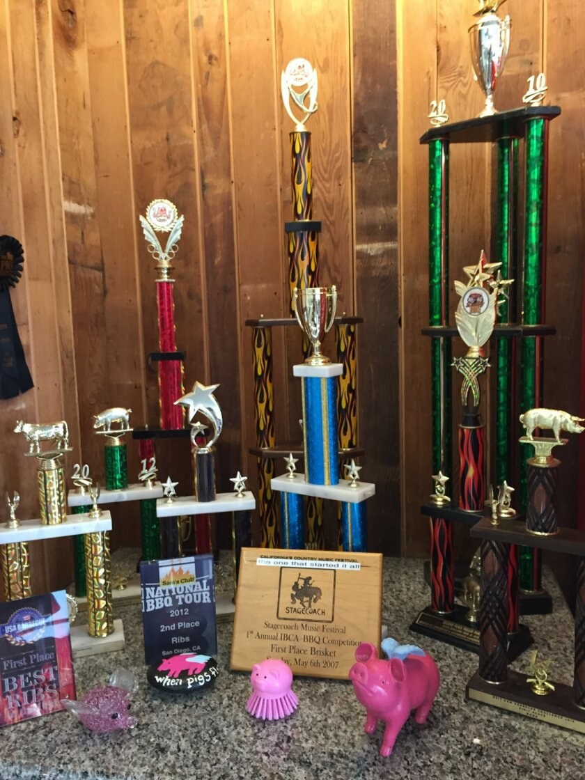 A shelf of trophies and plaques celebrating the award-winning barbecue at When Pigs Fly BBQ restaurant in Vista.