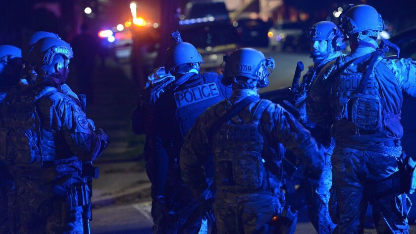 A SWAT team prepares to search the neighborhood where a police officer was fatally shot Friday in New Kensington, Pa.