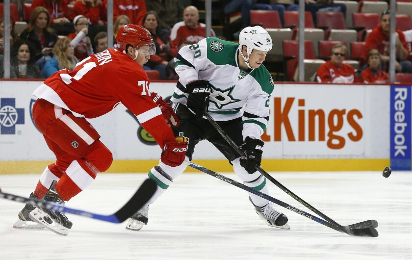 Detroit Red Wings center Dylan Larkin (71) knocks the puck from Dallas Stars center Cody Eakin (20) in the first period of an NHL hockey game, Sunday, Nov. 8, 2015 in Detroit. (AP Photo/Paul Sancya)