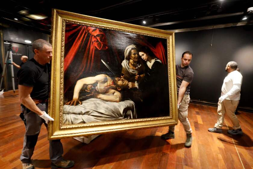 "Workers carry ""Judith and Holofernes,"" believed to be by Caravaggio, to a public presentation at the Drouot auction house in Paris earlier this month."