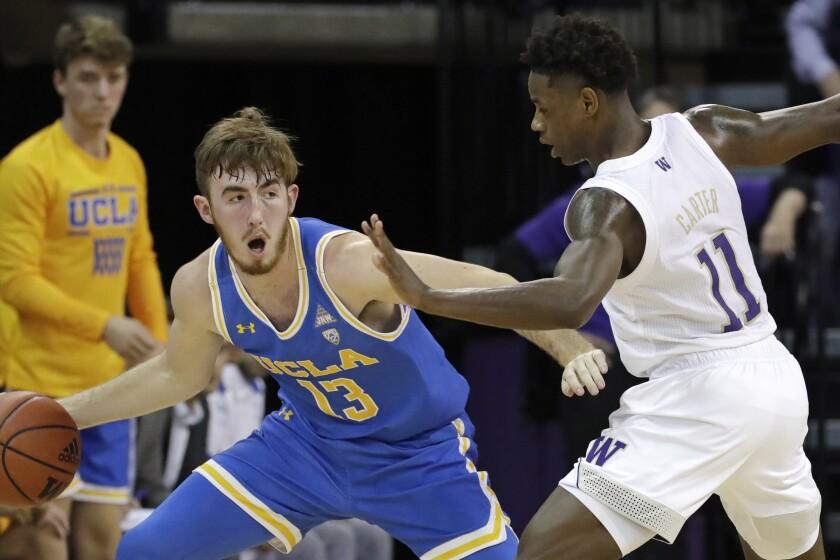UCLA's Jake Kyman looks to pass around Washington's Nahziah Carter.