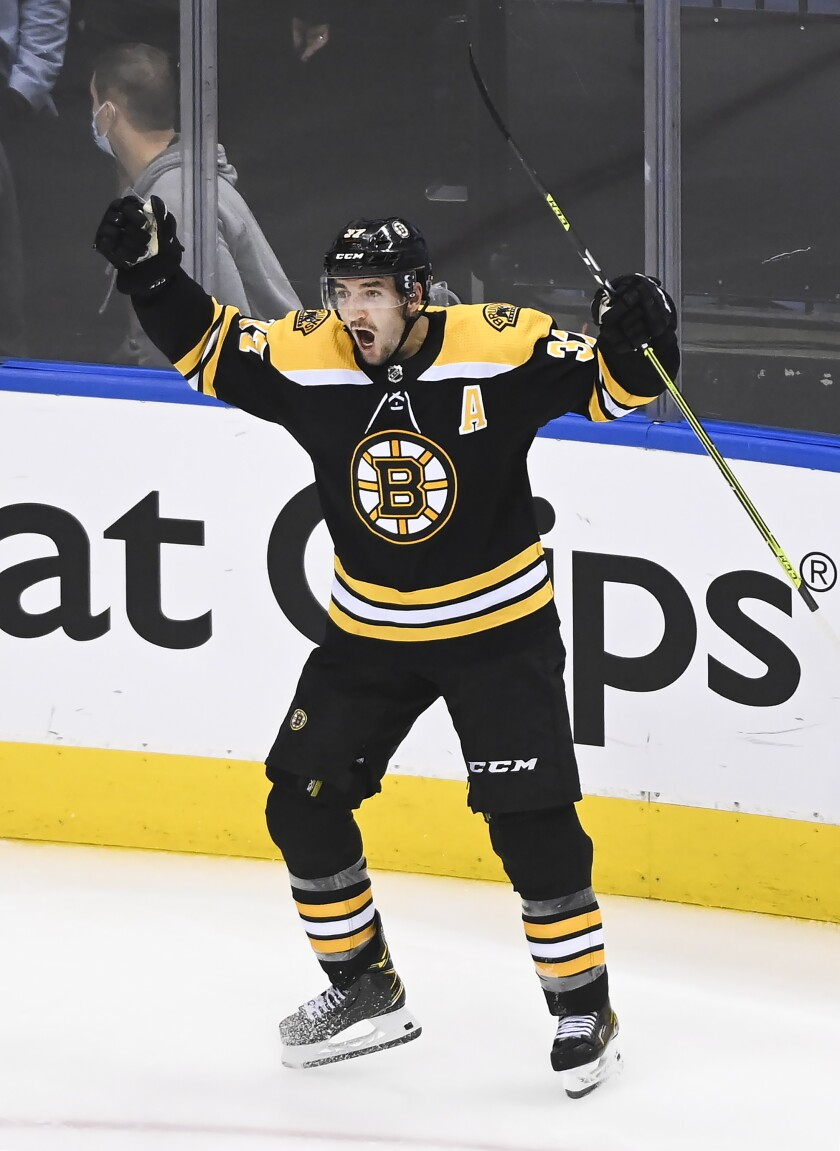 Boston Bruins center Patrice Bergeron (37) reacts after scoring the game winning goal against the Carolina Hurricanes during the second overtime period of an NHL hockey Eastern Conference Stanley Cup playoff game in Toronto, Wednesday, Aug. 12, 2020. (Nathan Denette/The Canadian Press via AP)