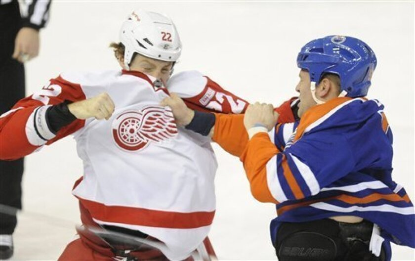 Edmonton Oilers' Ben Eager, right, fights, with the Detroit Red Wings' Mike Commodore during first period NHL hockey game action in Edmonton, Alberta, Saturday, Feb. 4, 2012. (AP Photo/The Canadian Press, John Ulan)