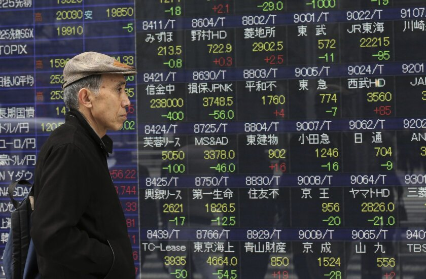 A man looks at an electronic stock board of a securities firm in Tokyo Friday, April 10, 2015. Japan's Nikkei retreated from the highest level in 15 years on Friday while other markets in the region advanced ahead of key data news from China. (AP Photo/Eugene Hoshiko)
