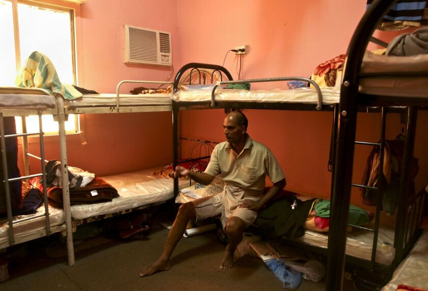 FILE - In this May 3, 2015, file photo taken during a government organized media tour, Kuttamon Chembadnan Velayi from Kerala, India, speaks to journalists while sitting on his bed in a room he shares with seven other Indian laborers in Doha, Qatar. Amnesty International said Thursday, May 21, that