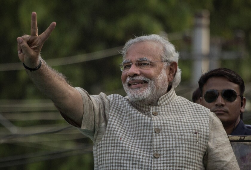 India's conservative party leader, Narendra Modi, flashes a victory sign before addressing supporters in Vadodara.