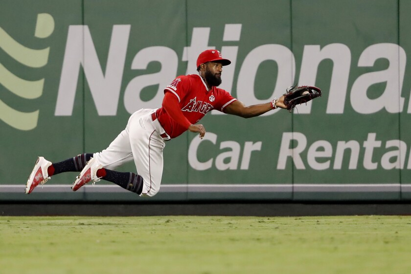 Angels center fielder Brian Goodwin leaps to catch a line drive.