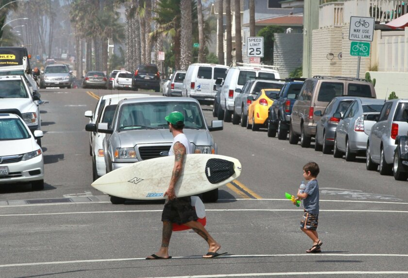 A man and child cross South Pacific Street in Oceanside, where many vacation rentals are located.