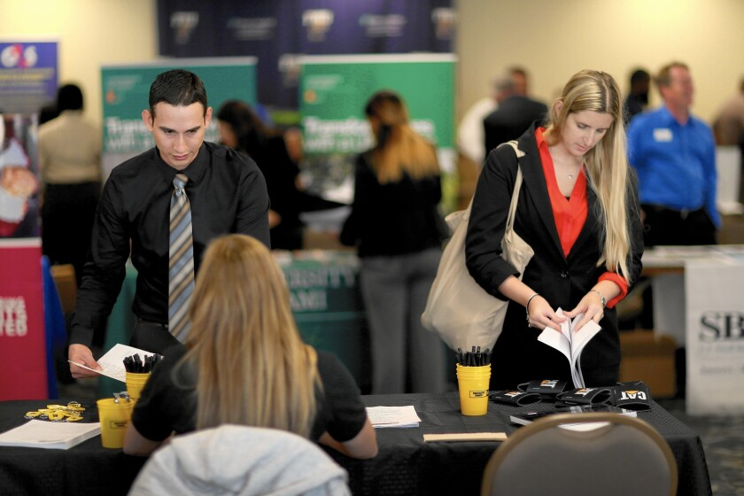 Antonio Sandoval and Pamela Springle search for positions in the civilian workforce at a veterans jobs fair in Miami this year.