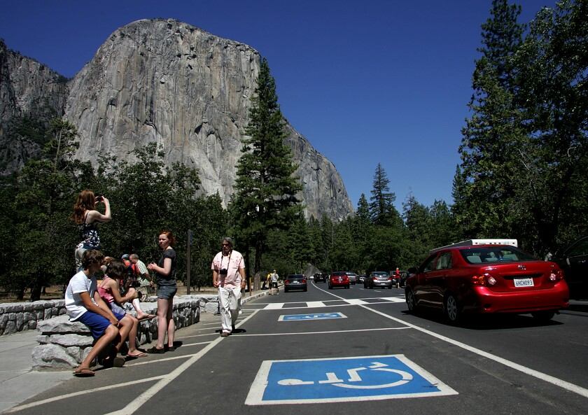 Tourists gather in a congested area of Southside Drive to view and take photos of El Capitan in Yosemite National Park in California. On busy days, more than 8,000 cars pass through Yosemite Valley.