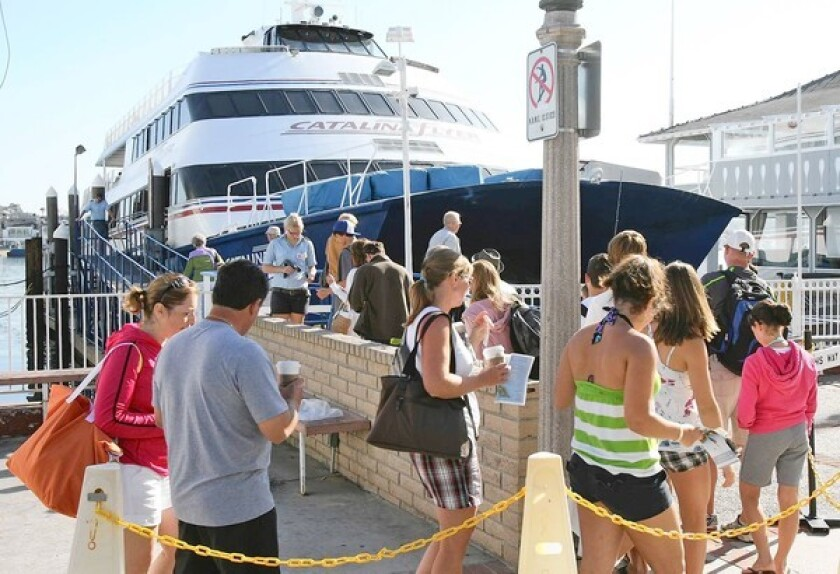 Passengers board the Catalina Flyer for a day trip from Newport Harbor. The boat, famous for giving tours to Catalina Island, may have to temporarily shut down operations after Labor Day in order to buy a new engine for its boat per state requirement.