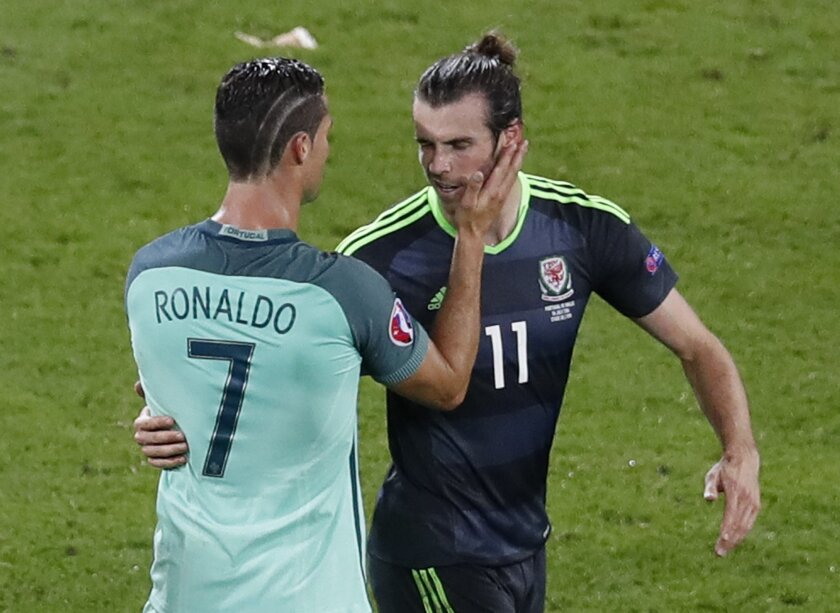 Portugal's Cristiano Ronaldo, left, comforts Wales' Gareth Bale after Portugal won 2-0  during the Euro 2016 semifinal soccer match between Portugal and Wales, at the Grand Stade in Decines-Charpieu, near Lyon, France, Wednesday, July 6, 2016. (AP Photo/Michael Sohn)