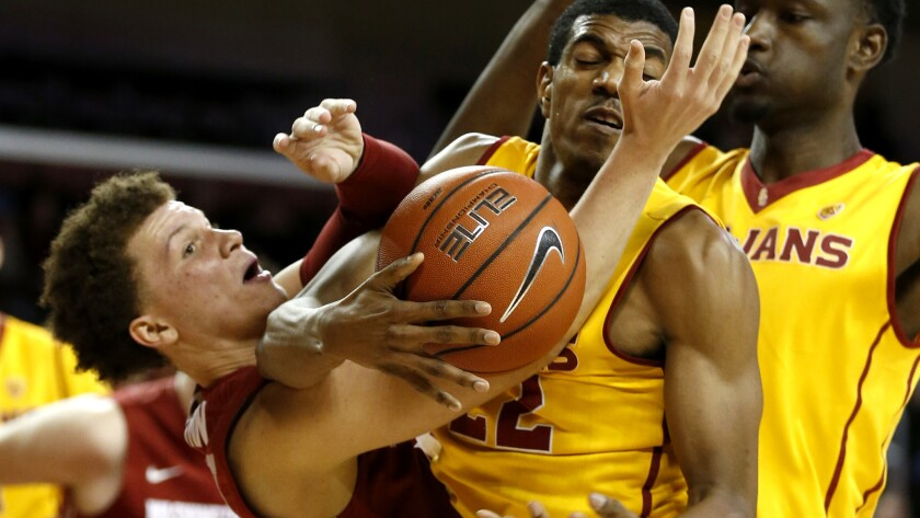 USC guard De'Anthony Melton, center, battles for a rebound against Washington State guard Malachi Flynn during the second half Wednesday.