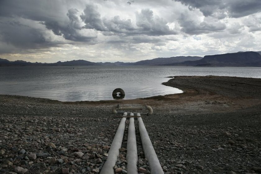 Water intake pipes that were once underwater sit above the water line along Lake Mead in the Lake Mead National Recreation Area, Monday, May 18, 2015, near Boulder City, Nev. A series of storms in May are projected to keep Lake Mead's level high enough for the next two years to forestall potential