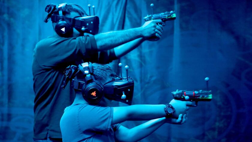 Knott's Berry Farm visitors Derek Phelps and his brother Tyrus, 8, play a round of VR Showdown in Ghost Town. Attractions that include a gaming element are increasingly popular at regional theme parks.
