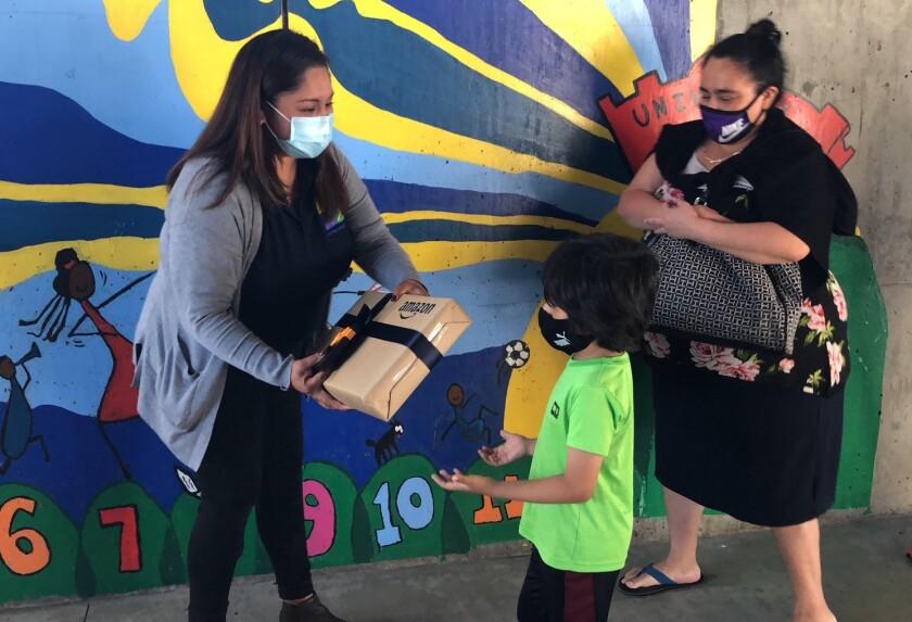 Jonathan, de 6 años, recibió su laptop de manos de Grace Sánchez, de la escuela Para Los Niños.