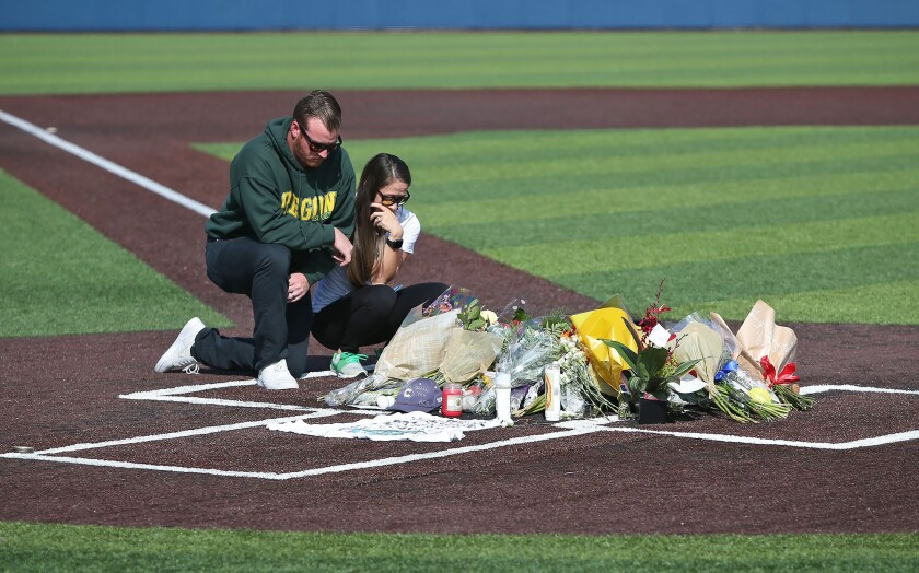 A couple pay their respects at a memorial shrine at home plate in honor of Orange Coast College baseball coach John Altobelli, who died with his wife, Keri, and daughter, Alyssa, in the helicopter crash that claimed the life of Kobe Bryant.