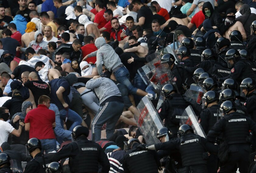 FILE - In this  Saturday, April 16, 2016 file photo, Serbian riot police officers clash with Red Star soccer fans during a Serbian National soccer league match between Red Star and Partizan, in Belgrade. Hooliganism is making a comeback, and the timing could be bad with four high-risk matches in th