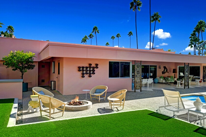 Designed by local architects Albert Frey and Robson Chambers, the pink-hued residence unfolds as a series of interconnected boxes. The home was built in 1964 for radio and TV owner Carl Haymond and his wife, Margaret. Listed for $2.995 million, the house features a series of aluminum screens that provide privacy while diffusing natural light. The screens were designed by John deKoven Hill, an associate of Frank Lloyd Wright. The single-story house features travertine and terrazzo tile floors, walls of glass and walnut built-ins. The steel cabinetry in the kitchen is original.
