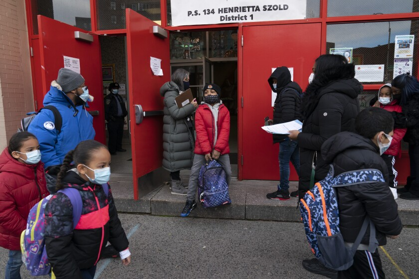 Students arrive at P.S. 134 Henrietta Szold Elementary School, Monday, Dec. 7, 2020, in New York. Public schools reopened for in-school learning Monday after being closed since mid-November. (AP Photo/Mark Lennihan)