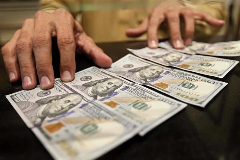 Un hombre sostiene unos billetes de dólar estadounidense. EFE/Archivo