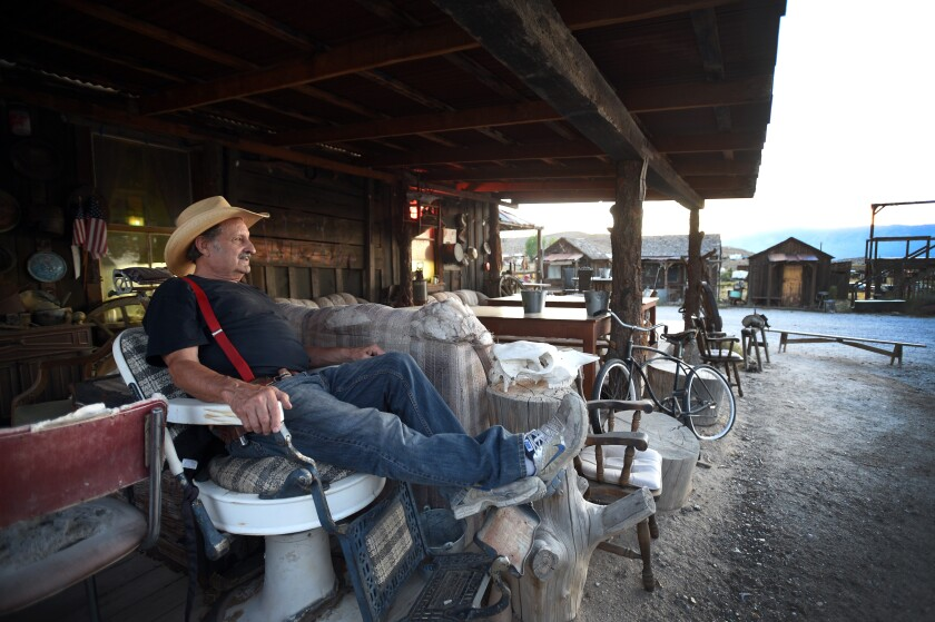 Proprietor Walt Kremin relaxes on the porch of his saloon in Gold Point, Nev., in July.