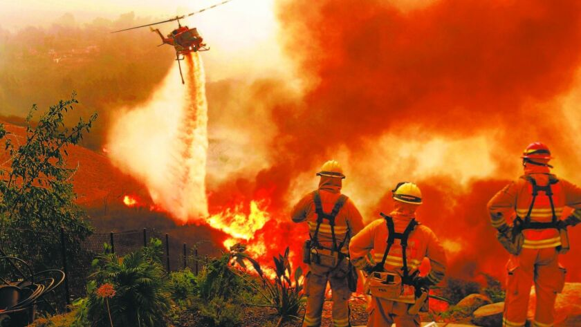 In an October 23, 2007 file photo, firefighters watch as a San Diego Fire helicopter drops water on a fire between Lake Hodges and Escondido.