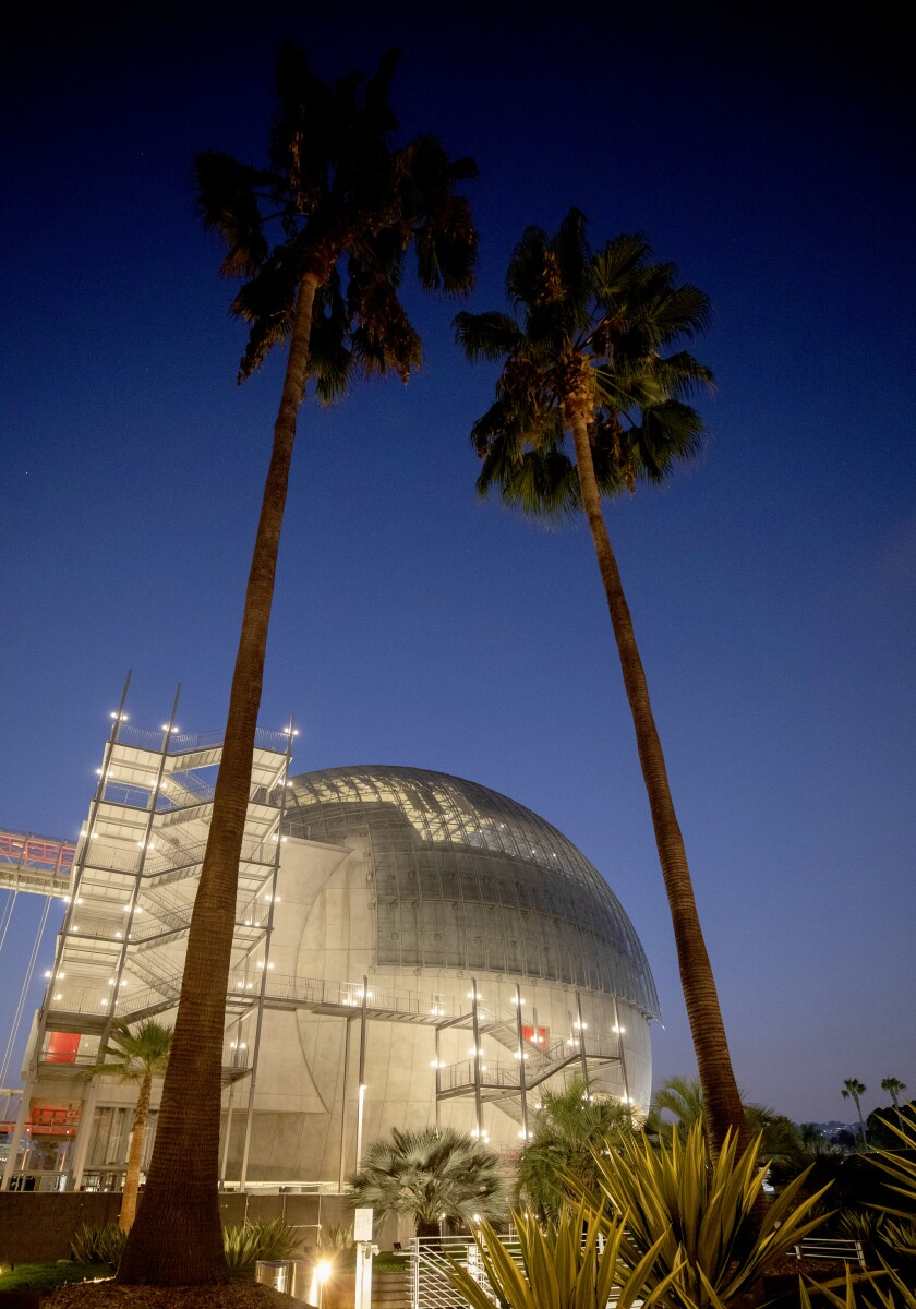 The Academy of Motion Pictures Museum at night, framed by two palm trees.