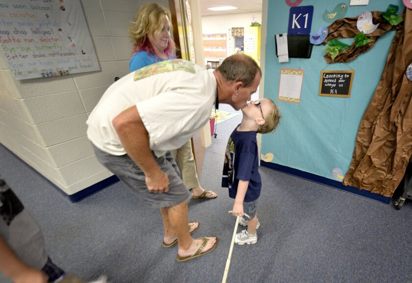 Students benefit from parents and teachers communicating well, a new study shows. Shane Warren kisses son Miles, 5, as he drops him off for his first day of school in North Augusta, S.C., as mom DeAnne looks on.