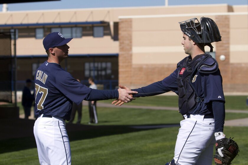 Pitcher Robbie Erlin greets catcher Austin Hedges during the first workout day of Padres spring training Wednesday in Peoria, Arizona.