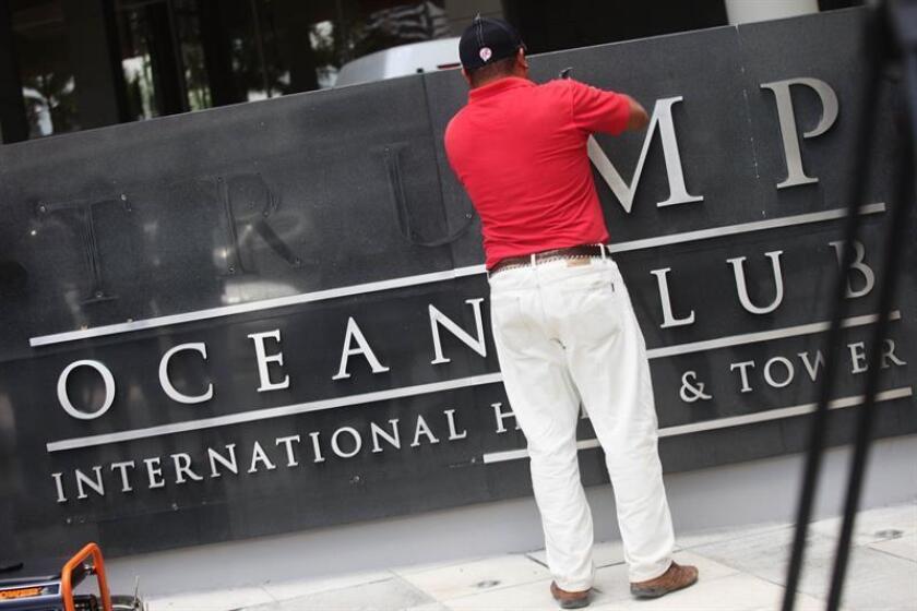Un trabajador retira el letrero del Trump Ocean Club, mientras unidades de la policía nacional y representantes del Órgano Judicial de Panamá realizan un operativo en el edificio el 5 de marzo de 2018, en Ciudad de Panamá (Panamá). EFE