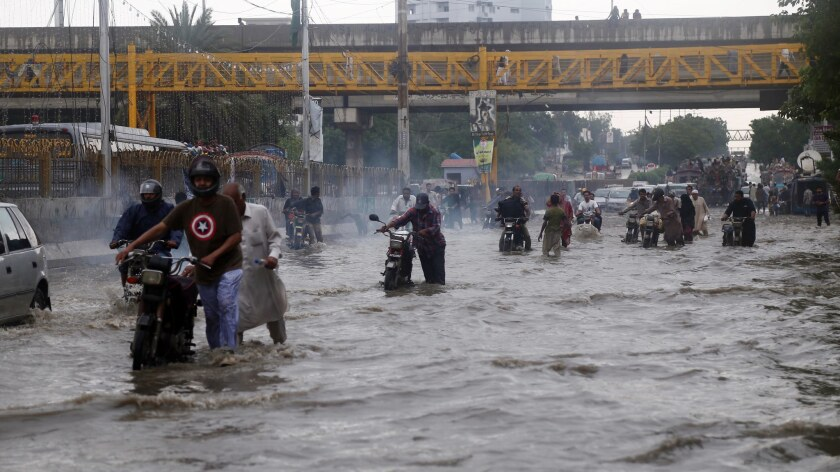 People make their way through flooded streets after heavy downpour in Karachi, Pakistan, on Aug. 31.