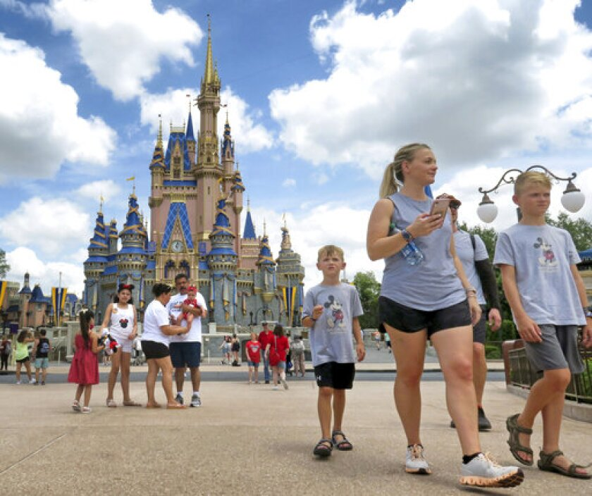 Guests walk past Cinderella Castle at the Magic Kingdom at Walt Disney World, in Lake Buena Vista, Fla., Monday, May 17, 2021, after Disney Co. eased face mask requirements over the weekend. Guests are allowed to go maskless in outdoor areas of the parks. Indoor attractions, shops and Disney transportation at the resort all still require masks. (Joe Burbank/Orlando Sentinel via AP)